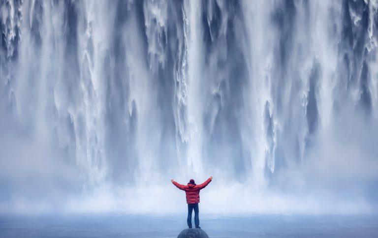 Afbeelding van iemand met handen gespreid voor een waterval